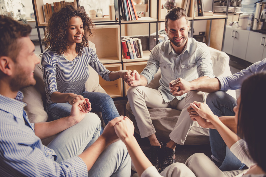 Group of people holding hands in therapy
